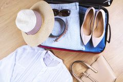 Open suitcase with casual woman clothes hat, sunglasses, white shirt, shoes, bag on wooden floor top view close up. Packing travel stock image