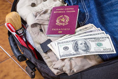 Open suitcase with clothes, personal effects, dollars, italian p Royalty Free Stock Photography