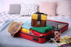 Open suitcase with different personal stuff. On bed Stock Images
