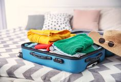 Open suitcase with different personal stuff. On bed Stock Photography