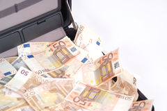 Open suitcase with money on white Stock Photos