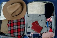 Open suitcase packed for travelling. Winter vacations and holida Stock Photos