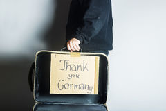 Open suitcase of refugee with message thank you Germany on cardb Royalty Free Stock Photos