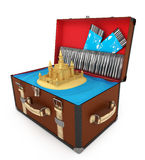 Open suitcase with sand castle and plane tickets Royalty Free Stock Photo