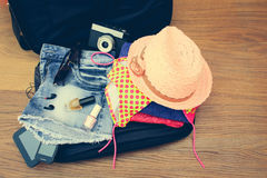 Open the suitcase with tourist things: women's hat, swimsuit, camera, denim shorts, dresses, sunglasses, perfumes, nail polish Royalty Free Stock Images