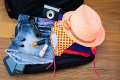 Open the suitcase with tourist things: women's hat, swimsuit, camera, denim shorts, dresses, sunglasses, perfumes, nail polish, Royalty Free Stock Images