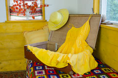Open suitcase with yellow  dress straw female hat Royalty Free Stock Images
