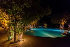 Open swimming pool with trees around it in evening royalty free stock photography