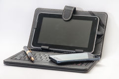 Open tablet with keyboard and Android mobile phone Stock Images