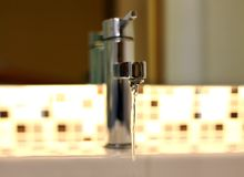 Open tap water with chrome faucet. Open chrome faucet tap with running water Royalty Free Stock Photos