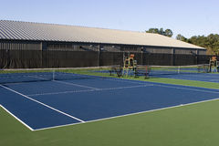 Open Tennis Courts. A few blue cement outdoor tennis courts with a tennis center behind them Stock Images