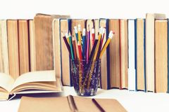 Open textbook, notebook, stack of books education back to school background and pencils in plastic holder with copy space for text royalty free stock photos