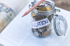 Open textbook, pencil, and coins in a glass bottle on the table. The concept of intelligence comes from education. selective focus Royalty Free Stock Images