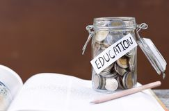 Open textbook, pencil, and coins in a glass bottle on the table. The concept of intelligence comes from education. selective focus Royalty Free Stock Image