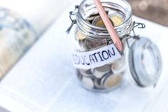 Open textbook, pencil, and coins in a glass bottle on the table. The concept of intelligence comes from education. selective focus Royalty Free Stock Photos