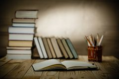 Textbooks and books on a wooden table. Open textbooks on wood desk with blurred focus for education background. Back to school concept Royalty Free Stock Photography
