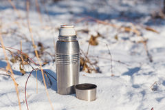 Open thermos with hot tea. In the snow in the winter Royalty Free Stock Photos