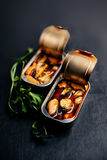 Open tin can with conserve food over black background. Mussels. Tin appetizer close up Royalty Free Stock Image