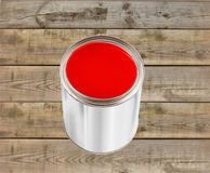 Open tin can with red paint on wooden table Royalty Free Stock Photo
