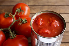 Open tin of chopped tomatoes. Open tin of chopped tomatoes with whole fresh unfocused tomatoes behind. Wood surface royalty free stock image