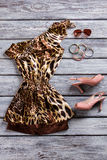 Open toe heels and dress. Leopard dress and sunglasses. Evening clothes on gray shelf. Girl's prom apparel with accessories Royalty Free Stock Photos