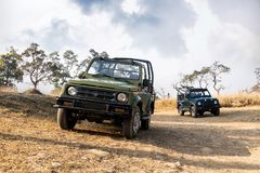 Open-top car on the field road. Competition off road and rough terrain. The Safari vehicles against the background sky with clouds. Autumn landscape Stock Photography