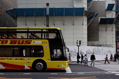An open top Hato tourist bus waits at a Ginza scramble crossing in front of the under-demolition Sony Building. An open top tourist bus operated by Hato Bus Stock Photo