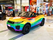 Open Top Land Rover Painted in Gay Pride Rainbow Colours. An open top Range Rover, decorated in the gay pride rainbow colours, on display in indoor shopping Stock Images