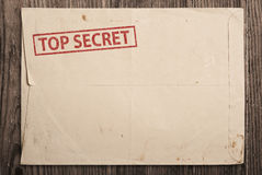 Open top secret envelope on table. Open yellow envelope with top secret stamp and papers, on wooden table, clipping path Stock Image