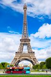 An open top tour bus stops in front of the Eiffel Tower in Paris. PARIS,FRANCE - JULY 30,2017 : An open top tour bus stops in front of the Eiffel Tower in Paris Royalty Free Stock Photography