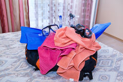 Open travel bag closeup. Open travel bag with flippers on bed closeup Royalty Free Stock Images