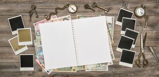 Open travel journal, polaroid photo frames, cash money. Open travel journal, polaroid photo frames, kompass, cash money various currency banknotes royalty free stock photos
