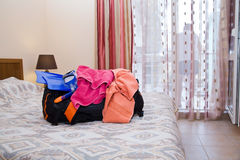 Open traveling bag with things. In room on bed Royalty Free Stock Photo