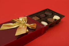 Open tray of chocolates. Open tray or boxy of chocolates decorated with ribbon, red background Stock Image
