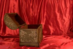 Open Treasure Chest. A treasure chest against red satin royalty free stock images