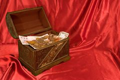 Open Treasure Chest. A treasure chest against red satin stock image