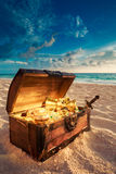 Open treasure chest on the beach. Open treasure chest with shinny gold royalty free stock image
