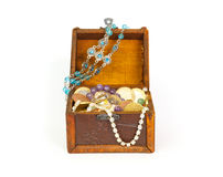 Open treasure chest with bracelets, coins, rings and pearls Stock Photo