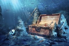 Open treasure chest with bright gold underwater. Photo of open treasure chest with shinny gold underwater