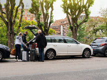 Open trunk people putting luggage in large trunk. STRASBOURG, FRANCE - MAY 7, 2017: Group of seniors and adults loading luggage in Skoda Octavia estate car Stock Photography