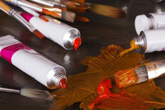 Open tubes of brown paint and brushes Royalty Free Stock Image