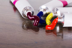Open tubes with coloured paint coming out Royalty Free Stock Photo