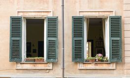 Open twin window views. Open windows of an apartment with flower decorations on the window sills Royalty Free Stock Images