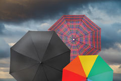 Open umbrellas with storm grey clouds Royalty Free Stock Images