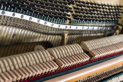 Open upright piano mechanism with strings and hammers. Selective focus royalty free stock image