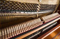 Open upright piano mechanism with strings and hammers. Selective focus stock photography
