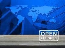 Open 24 urenpictogram op houten lijst over wereldkaart en stadstoren Stock Afbeeldingen