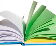 Open varicolored notebook lies on surface, horizontal closeup Stock Images