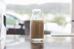 Open very small vintage retro glass bottle of milk with milk ins stock photos