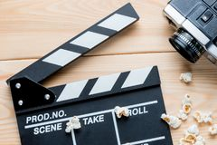 Open video clapper, retro video camera and salted popcorn top vi. Ew on wooden boards royalty free stock image
